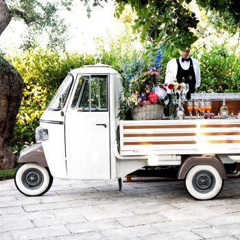 Categoria complementi noleggio per matrimoni e eventi in Puglia ape più piaggio dotata di piano appoggio in legno per servizio cocktail bar confettata rum e sigari wedding cake Che Scena